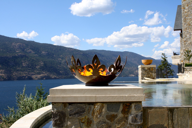 Fiery Fleur-de-lis 37 Inch Sculptural Firebowl™ Flanking Infinity Pool Over Lake Okanagan