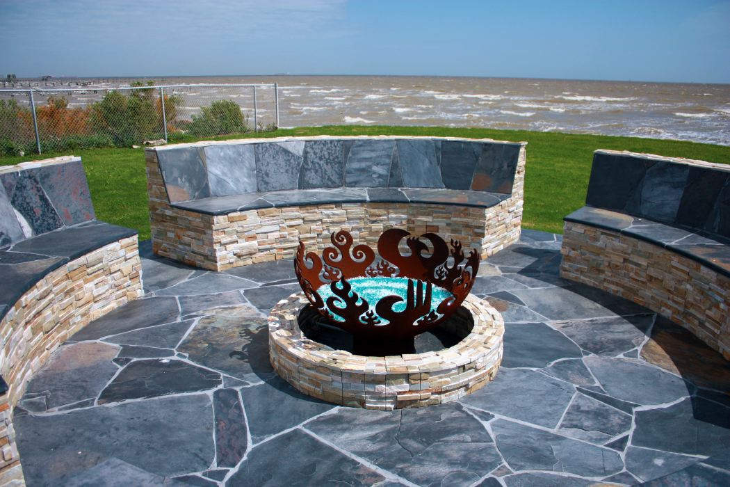 Stone benches and gas firebowl on waterfront