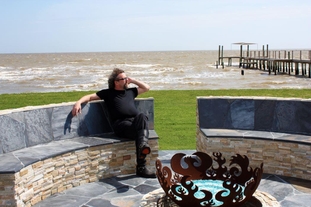 Artist John T. Unger seated by Great Bowl O' Fire on Galveston Bay