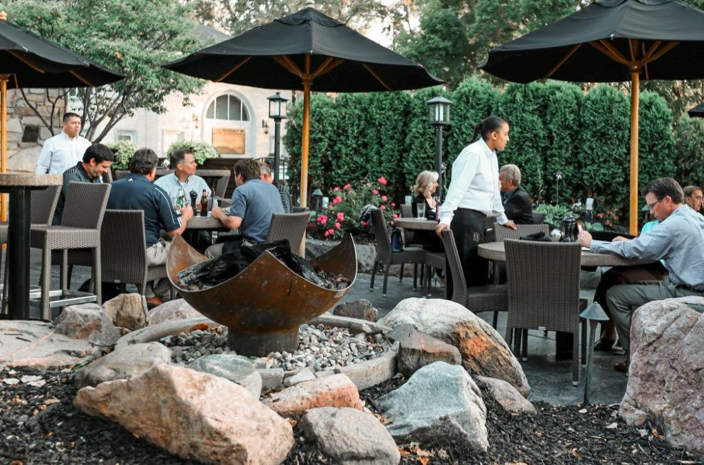 King Isosceles Sculptural Firebowl nestled among boulders between the entry and the patio at Redstone American Grill, Minnetonka, MN